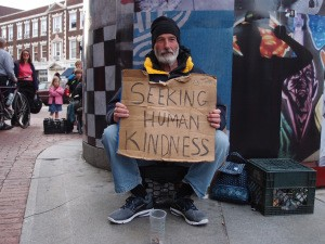 "Homeless man holding a sign that says, ""seeking human kindness."""